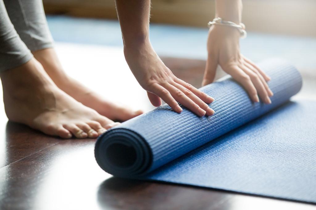 Bild på kvinna som rullar ut en yogamatta